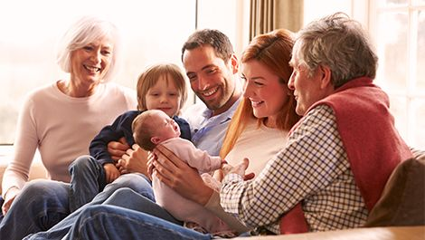 Happy family covered by voluntary life insurance plan through work.