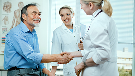 doctor shaking hands with patient covered under cancer insurance rates